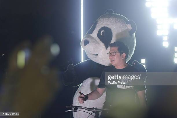 Panda mascot and Quezon City mayor Herbert Bautista is posing for a photo while pedaling a bike as it lights up the Philippine LED map on the wall...