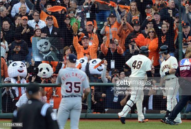Panda masks line the bottom row of the stands as Pablo Sandoval of the San Francisco Giants returns to the dugout after hitting a home run off Justin...
