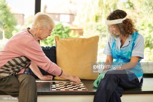 pandemic caregiver playing games - glove stock pictures, royalty-free photos & images