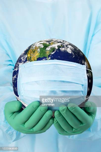 concept pandémique - mains de médecin dans des gants retenant la planète terre dans un masque médical - maladie infectieuse photos et images de collection