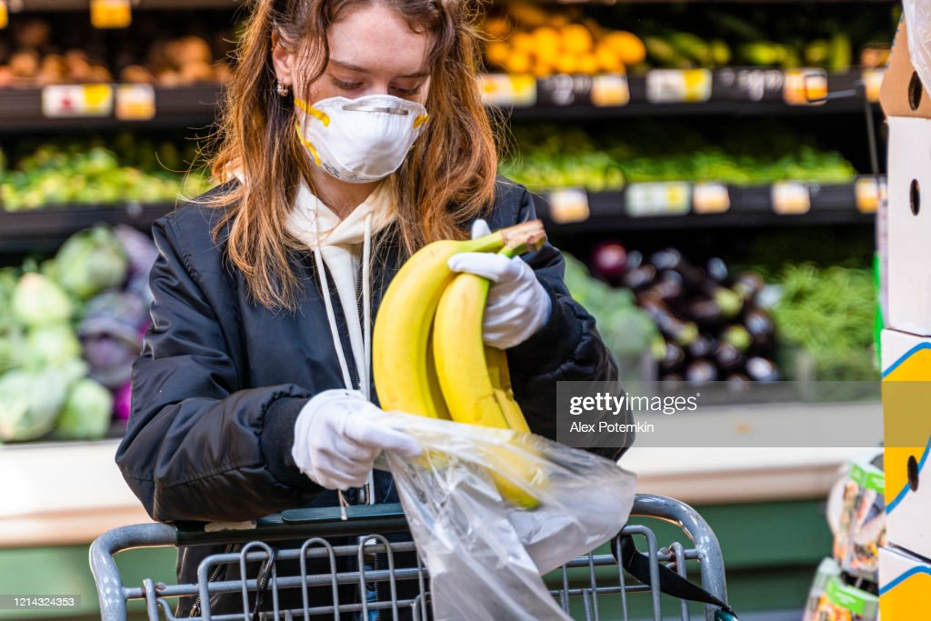 Pandemic times shopping. A young woman wearing a protective mask and gloves buying babanas in a supermarket. : Stock Photo