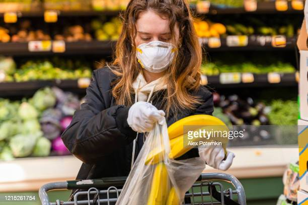 pandemic times shopping. a young woman wearing a protective mask and gloves buying babanas in a supermarket. - alex potemkin coronavirus stock pictures, royalty-free photos & images