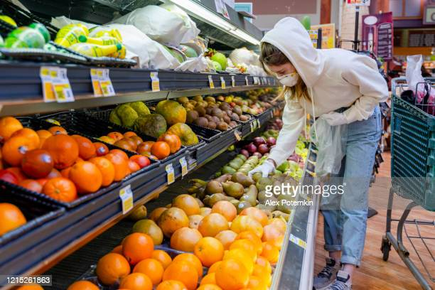 pandemic times shopping. a young woman wearing a protective mask and gloves buying fruits in a supermarket. - alex potemkin coronavirus stock pictures, royalty-free photos & images
