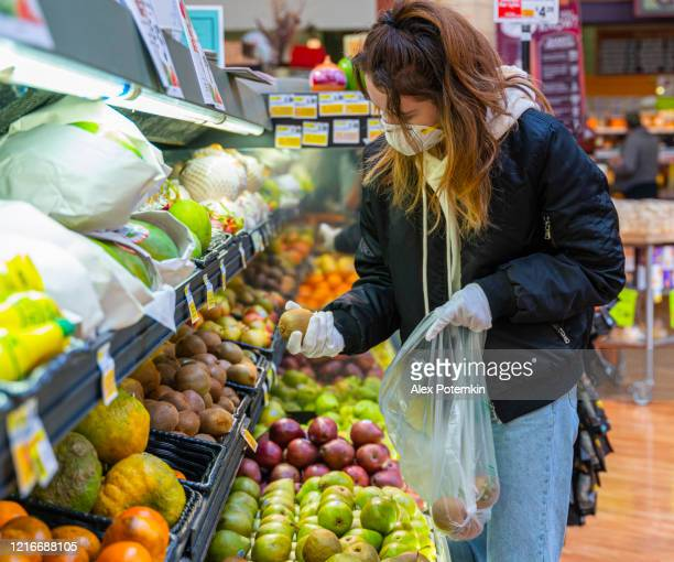 pandemic times shopping. a young woman wearing a protective mask and gloves buying food supplies, picking fruits in a supermarket. - alex potemkin coronavirus stock pictures, royalty-free photos & images