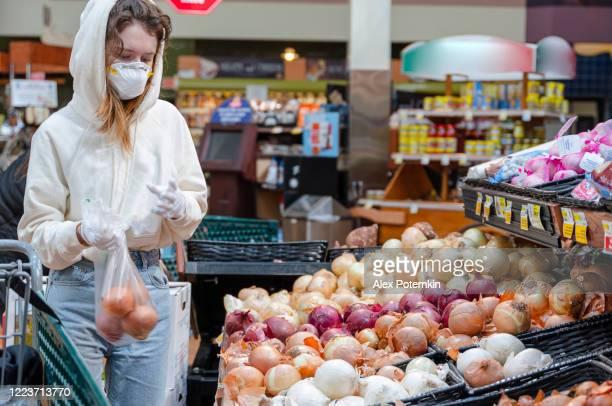 パンデミックタイムショッピング。スーパーマーケットで野菜を買う保護マスクと手袋を身に着けている若い女性。 - state of emergency ストックフォトと画像