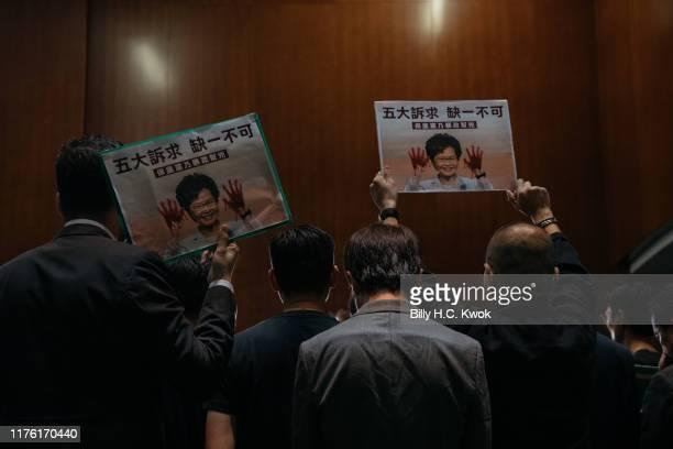 Pan-democratic legislators raise posters during a press conference after Hong Kong Chief Executive Carrie Lam left the Legislative Council on October...