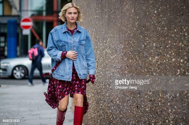 Pandora Skies wearing dress denim jacket red boots outside Christopher Kane during London Fashion Week September 2017 on September 18 2017 in London...
