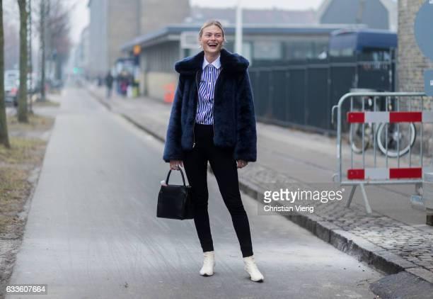 Pandora Sykes wearing a navy fur jacket striped button shirt outside By Malene Birger during the Copenhagen Fashion Week Autumn/Winter 17 on February...