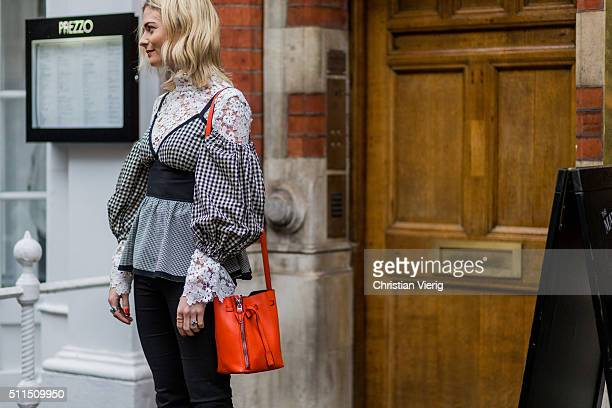 Pandora Sykes wearing an orange Diesel bag and a plaid shirt and white floral blouse seen outside Julien Macdonald during London Fashion Week...