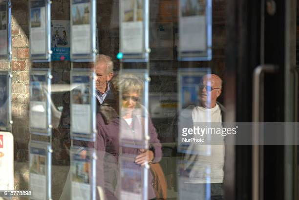 A pane of glass reflects light as people pass an estate agent on October 19 2016 in Manchester England The United Kingdom's finance industry...