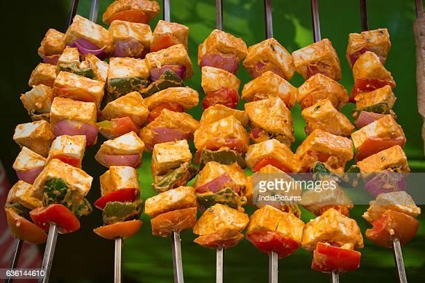 Paneer Kababs Hanging On Skewers For Grilling