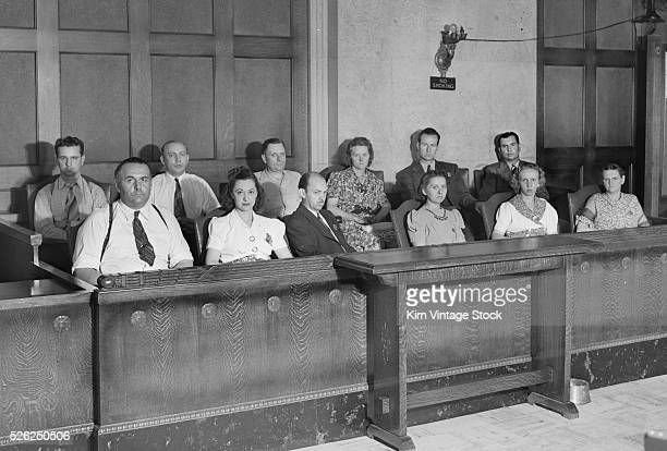 Panel of men and women with serious looks on their faces sits in the jury box.
