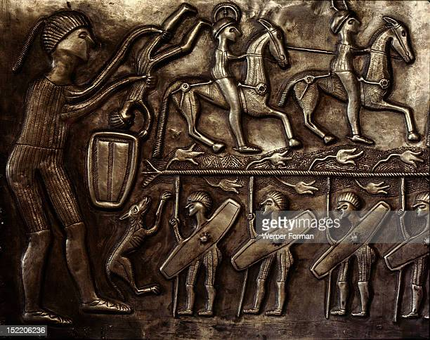 Panel of the Gundestrup cauldron Scene of human sacrifice while armed men make ready for war The ritual sacrifice is presumably associated with the...
