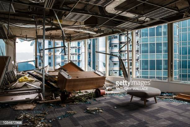 TOPSHOT Panels and debris from a collapsed ceiling are seen with blown over pieces of furniture in a company office in a harbourside commercial...