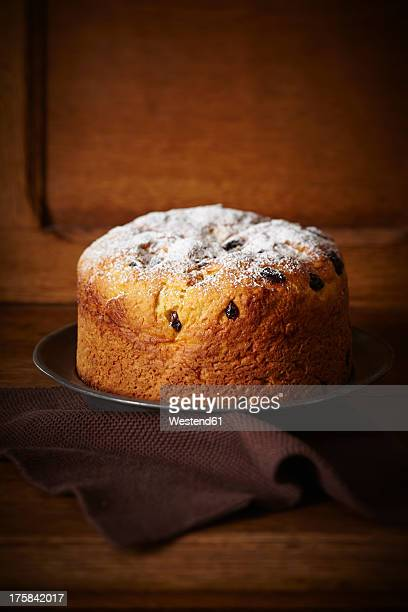 panettone cake with cranberries and icing sugar on plate - panettone stock pictures, royalty-free photos & images
