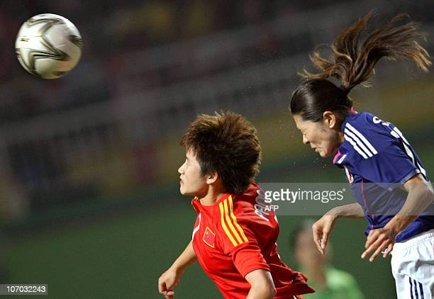 Pang Fengyue of China jumps for the ball with Sawa Homare of Japan during the women's semifinal match at the 16th Asian Games in Guangzhou on...