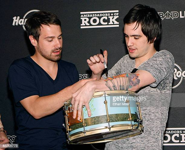 Panic at the Disco bassist Jon Walker and frontman Brendon Urie sign a drum as they donate it to the Hard Rock Cafe Las Vegas during a preconcert...