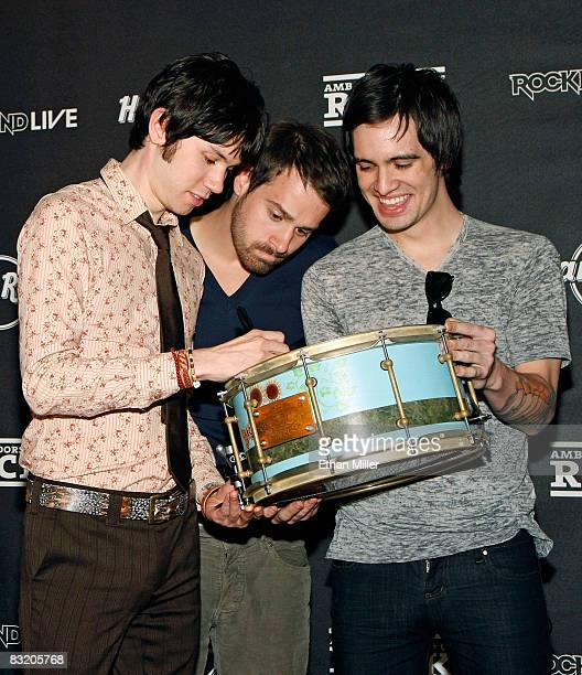 Panic at the Disco guitarist Ryan Ross bassist Jon Walker and frontman Brendon Urie sign a drum as they donate it to the Hard Rock Cafe Las Vegas...