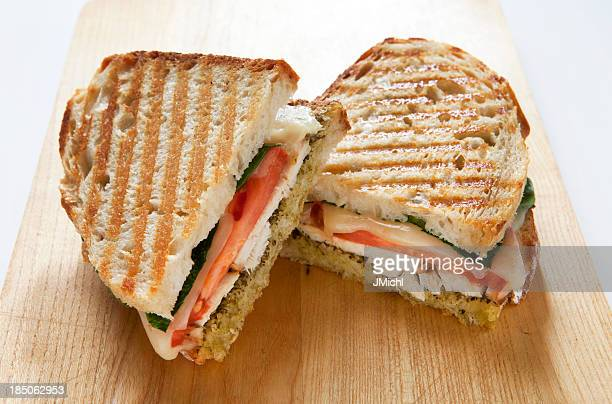 Panini with Chicken and Pesto on a Wooden Cutting Board.