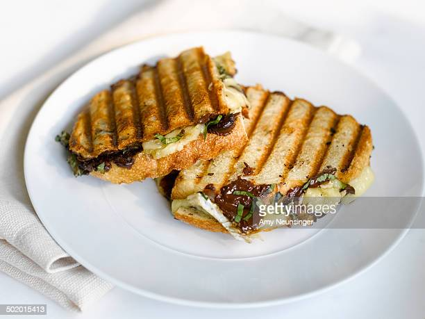 panini with chocolate, brie and basil. - brie stockfoto's en -beelden