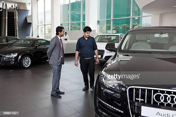 Pankaj Sharma deputy manager of sales at the Audi Delhi South dealership left speaks with customer Saurabh Kochar about Volkswagen AG's Audi Q7...