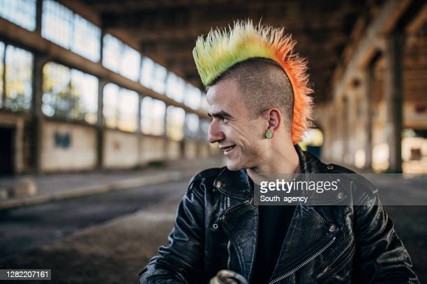 panker with colorful coiffure sitting in abandoned warehouse and drinking beer - mohawk stock pictures, royalty-free photos & images