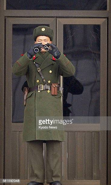 Panmunjom South Korea A North Korean soldier holds binoculars in front of a building on the North Korean side of the joint security area between...