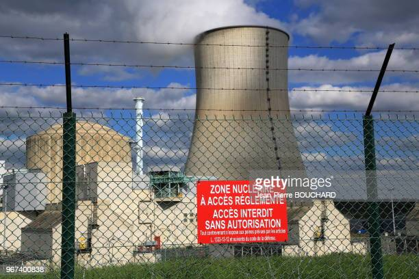 Panneau d'information sur lequel est écrit 'Zone nucléaire à accès règlementé accès interdit sans autorisation' accroché devant un grillage de...