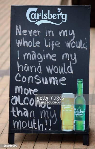 """Panneau d'un bar disant """"Jamais je n'aurais imaginé dans ma vie que ma main consommerait plus d'alcool que ma bouche"""" en référence au fort taux..."""