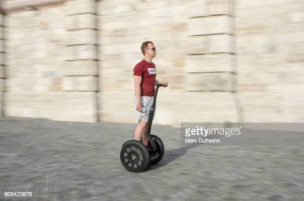 panning on a man on segway with huge tire during summer day - segway stock pictures, royalty-free photos & images