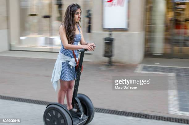 panning on girl on segway in street of downtown of budapest during summer day - segway stock pictures, royalty-free photos & images
