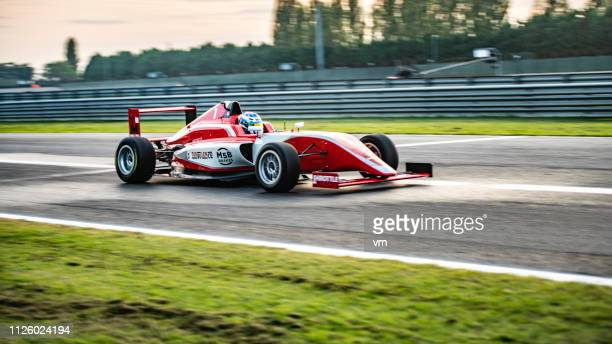 panning shot of a red formula car - grand prix motor racing stock pictures, royalty-free photos & images