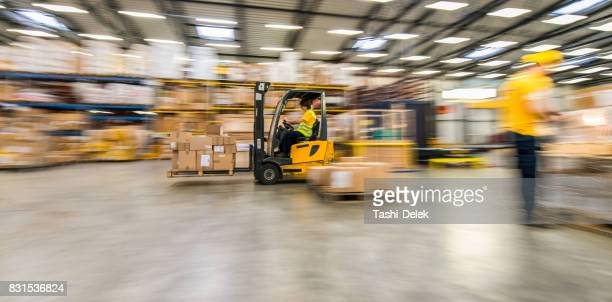 Panning Shot Of Moving Forklift In A Warehouse