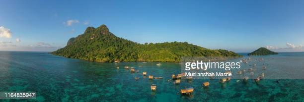 panorama aerial view using drone the sea gypsy stilt house at water village located in tatagan mabul island, semporna, sabah, malaysia. - kota kinabalu stock pictures, royalty-free photos & images