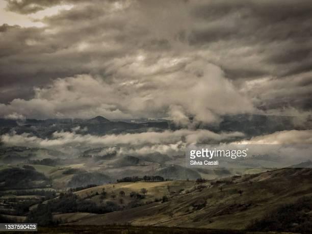 panorama collinare in inverno con nuvole basse e cielo minaccioso - silvia casali bildbanksfoton och bilder