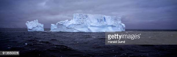 Panorama of a large blue colored iceberg floating in the Antarctic Ocean.