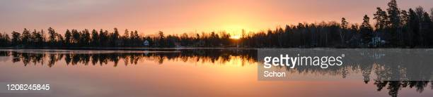 panorama of a sunrise at a mirrored lake with trees and houses in the background - tela grande - fotografias e filmes do acervo