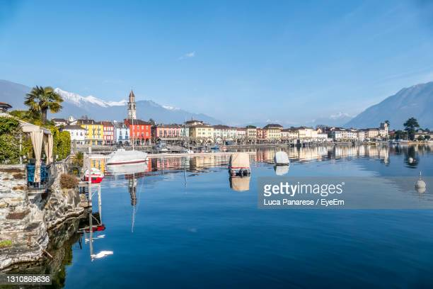 panorama of ascona with houses with colorful facades reflecting on lake maggiore - ascona stock pictures, royalty-free photos & images