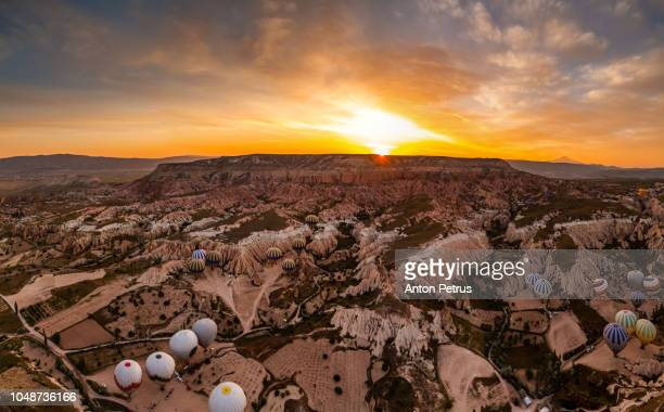 Panorama of balloons at sunrise over the beautiful landscape in Cappadocia, Turkey