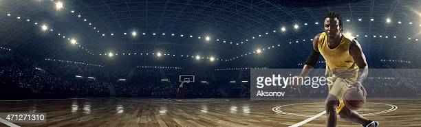 Panorama of basketball stadium under lights with player