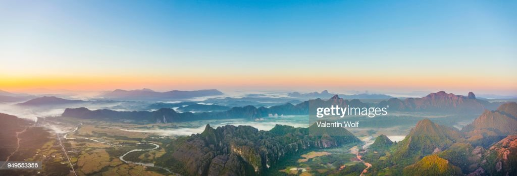 Panorama of karst mountains with mist at sunrise, Vang Vieng, Vientiane Province, Laos : Stock Photo