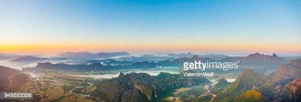 Panorama of karst mountains with mist at sunrise, Vang Vieng, Vientiane Province, Laos