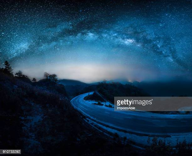 panorama of milky way above the mountainous landscape with the curve road at night