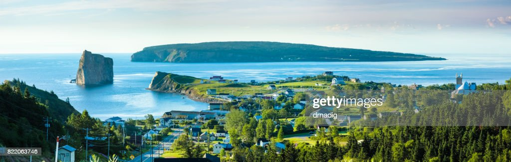 Panorama of Perce Rock in Quebec, Canada with pine trees in the foreground, and blue waters of the Gulf of St. Lawrence : Stock Photo