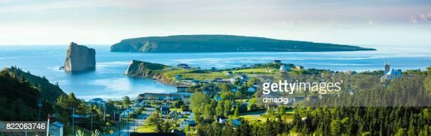Panorama von Perce Rock in Quebec, Kanada mit Pinien in den Vordergrund und blaue Wasser des St.-Lorenz-Golf
