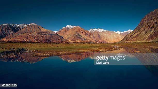 Panorama of reflected mountains on a lake near the Nubra valley in Ladakh Jammu and Kashmir India