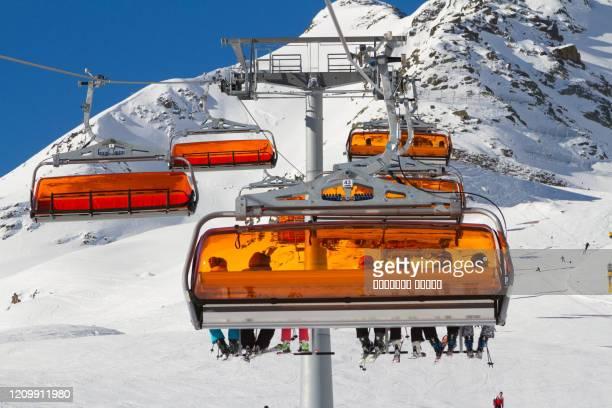 panorama of ski resort in soelden, tirol, austria. bright orange ski carriage and skiers. alps mountains. - sölden stock-fotos und bilder
