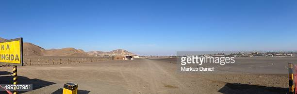 CONTENT] Panorama of the Airport in Naza Peru Looking toward the desert mountains on the left side and the runway and air plane parking spaces on the...