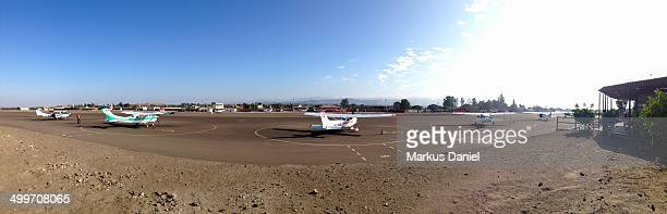 Panorama of the Airport in Nazca , Peru on a sunny day with blue sky showing parked planes and the main airport building to the very right.