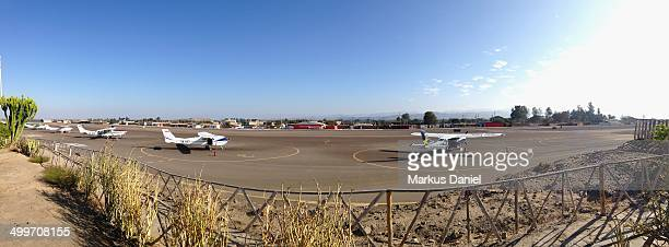 Panorama of the Airport Nazca , Peru on a sunny day with blue sky showing parked planes in the front and back with the runway in the middle.